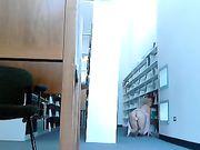 Una ragazza è nuda in libreria e sta masturbando